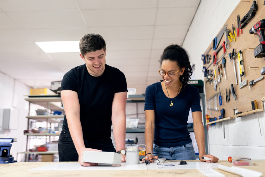 Two young people working on a project together in a maker's space