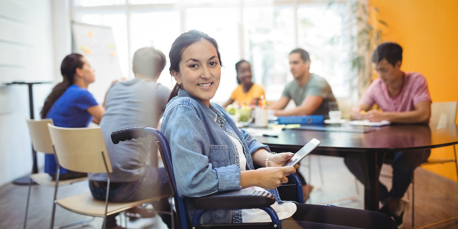 Young female adult, smiling, seated in a wheelchair and using digital tablet. Behind is a group of professionals working at a conference table.